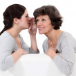 Woman telling her mother a secret — Stock Photo
