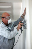 Man wearing mask and goggles whilst sanding wall — Stock Photo