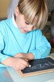 Little boy writing on a slate — Stock Photo
