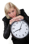 Blond businesswoman leaning on large clock — Stock Photo