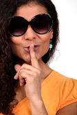 Mixed-race woman with sunglasses asking for silence — Stock Photo