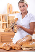 Assistant in a bakery offering poppy seeded baguettes — Stock Photo