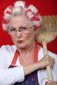 Senior woman holding a broom — Stock Photo