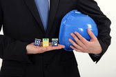 Businessman holding a hard hat and letter blocks — Stock Photo