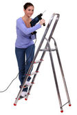 Woman on a stepladder with a powerdrill — Stock Photo