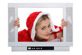 Woman in festive costume escaping from television — Stock Photo