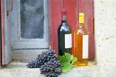 Two bottles of wine on rustic windowsill — Stock Photo