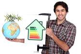 Artesano sosteniendo una etiqueta de consumo de energía y un globo con la planta verde en él — Foto de Stock