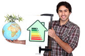 Craftsman holding an energy consumption label and a globe with green plant on it — Foto de Stock