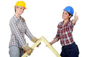 Two women with wooden truss — Stock Photo