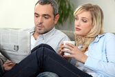 Couple with newspaper and coffee cup — Stock Photo