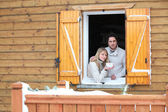 Couple looking out from chalet window — Stock Photo