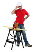 Carpenter stood with plank of wood on workbench — Stock Photo