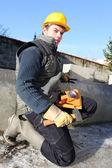 Mason kneeling by wall with lump hammer — Stock Photo