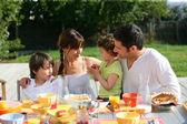 Familia almorzando afuera en un día soleado — Foto de Stock