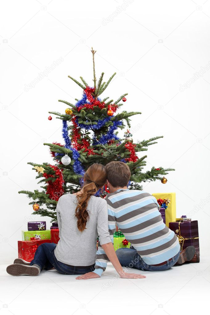 Couple sitting in front of a Christmas tree — Stok fotoğraf #10901941