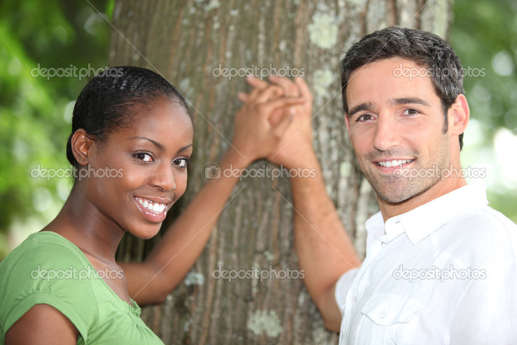 Affectionate couple stood by tree  Stock Photo #10908862