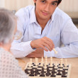 Stock Photo: Grandmplaying chess with grandson