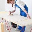 Woman pasting wall paper — Stock Photo