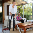 Woman vacuuming in senior woman's house — Stock Photo