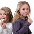 Stock Photo: Little girls eating candy