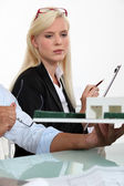 A blonde woman dressed in suit and a man looking a house scale model — Stock Photo