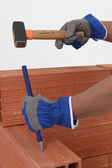 Man chiseling away at brick — Stock Photo