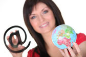Woman with at sign and globe — Stock Photo