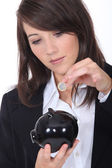 Young woman putting euros into a piggy bank — Stock Photo