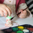 Stock Photo: Child painting plaster figurine