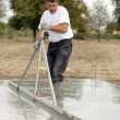 Foto Stock: Builder smoothing concrete foundation