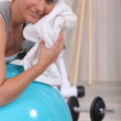 Woman in the gym wiping her face — Stock Photo
