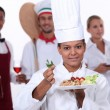 Foto Stock: Female chef presenting plate
