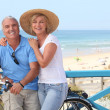 Mature couple with bikes by the beach — Stock Photo