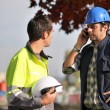 Construction workers on site with a phone — Stock Photo #10968657