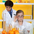 Children doing chemistry experiments with orange juice — Stock Photo