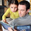 Father and daughter reading a book — Foto de Stock