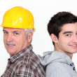 Tradesman standing back to back with his apprentice — Stock Photo #10969727