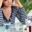 Woman with headache taking her medication — Stock Photo #10969898