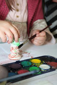 Child painting a plaster figurine — Stock Photo