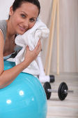 Woman in the gym wiping her face — Stockfoto