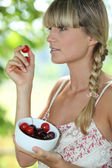 Blonde woman eating cherries — Stock Photo