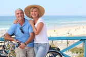 Mature couple with bikes by the beach — Foto de Stock