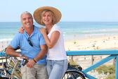älteres paar mit fahrrädern am strand — Stockfoto
