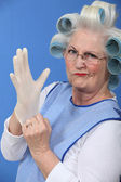 Granny with her hair in rollers putting on a latex glove — Stock Photo