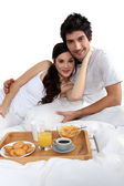 Couple eating breakfast in bed — Stock Photo