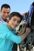 Vader en zoon verlijmen over motor — Stockfoto