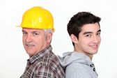 Tradesman standing back to back with his apprentice — Stock Photo