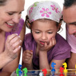 Young family playing a board game — Stock Photo #10972073