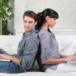 Couple sitting back to back while using their laptops — Stock Photo